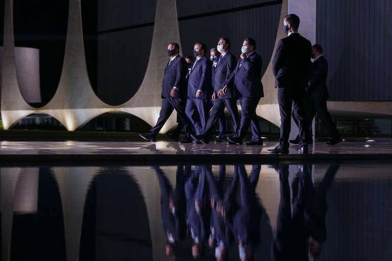 Homens de terno caminhando com o Palácio do Planalto ao fundo