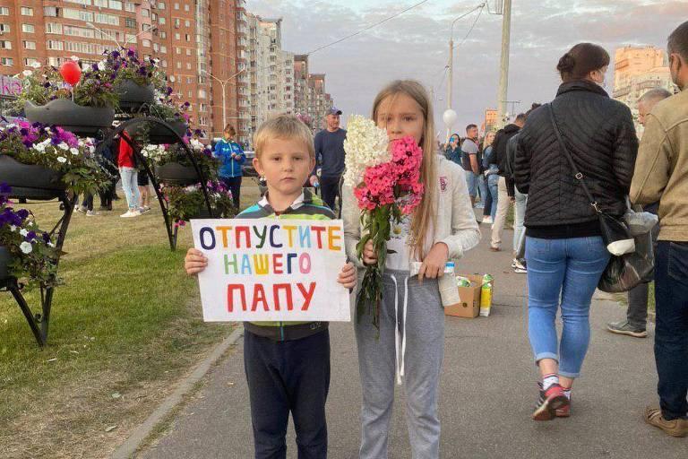 """Um menino que parece ter uns cinco anos e uma menina de talvez 9 seguram cartaz dizendo """"soltem o meu pai"""""""