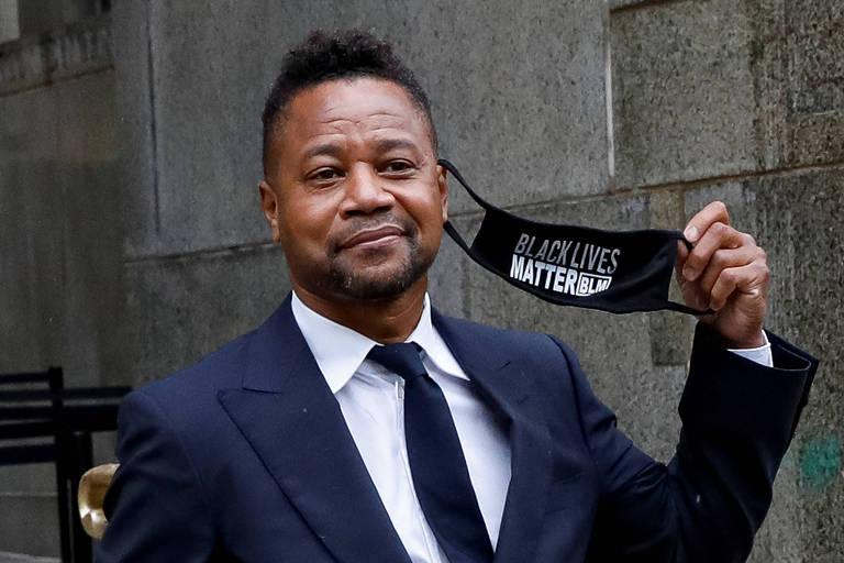 """Homem negro sorrindo mostrando sua máscara facial ao lado, que contém as palavras """"Black lives matter"""""""