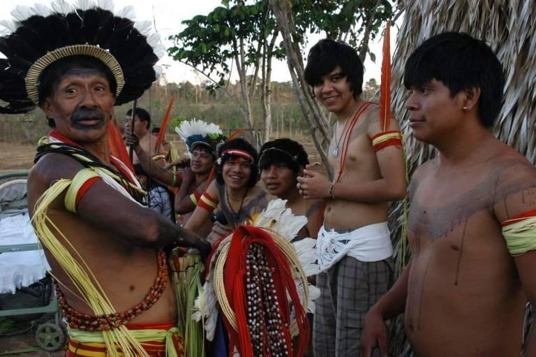 índio com cocar à esquerda fala com jovens indígenas