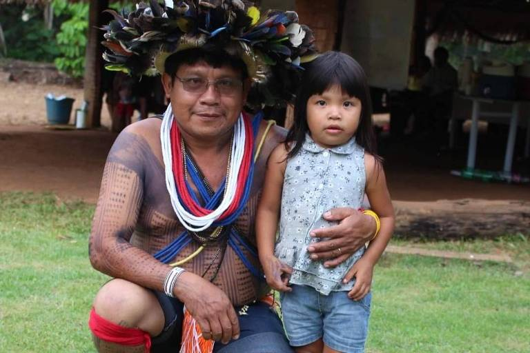 Renato Suruí, que morreu aos 43 anos em decorrência da Covid-19; o líder indígena aparece com trajes e pinturas típicas de seu povo, abraçado a uma menina indígena com blusa azul e bermuda jeans, num local gramado