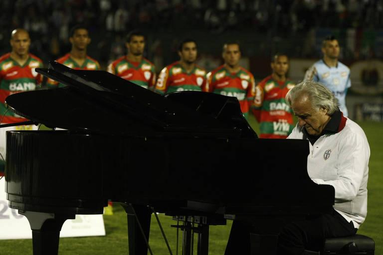 João Carlos Martins ao piano em primeiro plano, com os jogadores perfilados atrás