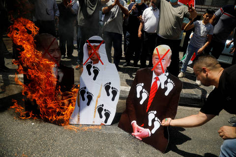 Palestinians burn cutouts depicting U.S. President Donald Trump and Abu Dhabi Crown Prince Mohammed bin Zayed al-Nahyan and Israeli Prime Minister Benjamin Netanyahu during a protest against the United Arab Emirates' deal with Israel to normalise relations, in Nablus in the Israeli-occupied West Bank August 14, 2020. REUTERS/Raneen Sawafta     TPX IMAGES OF THE DAY ORG XMIT: SUHAIB03