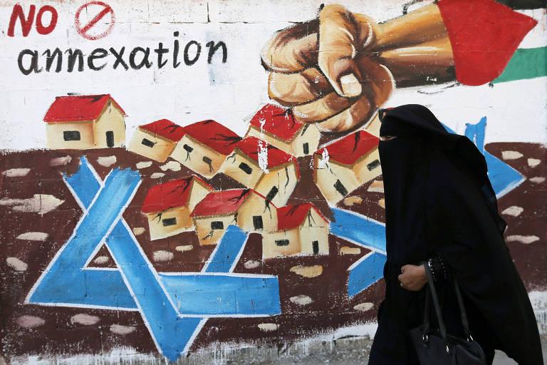 Mulher palestina caminha em frente a mural na Faixa de Gaza com mensagem contra a anexação de partes da Cisjordânia por Israel