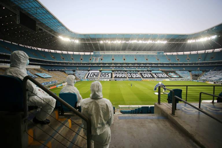 Funcionários da Arena do Grêmio com roupas de proteção na primeira rodada do Brasileiro