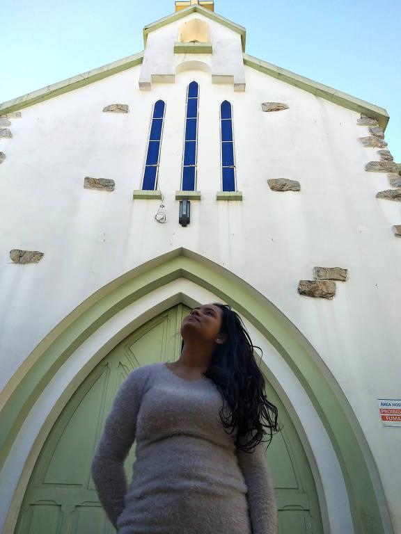 Mulher morena de cabelos longos usando blusa clara de manga longa posa diante de porta de igreja branca e azul, olhando para o céu