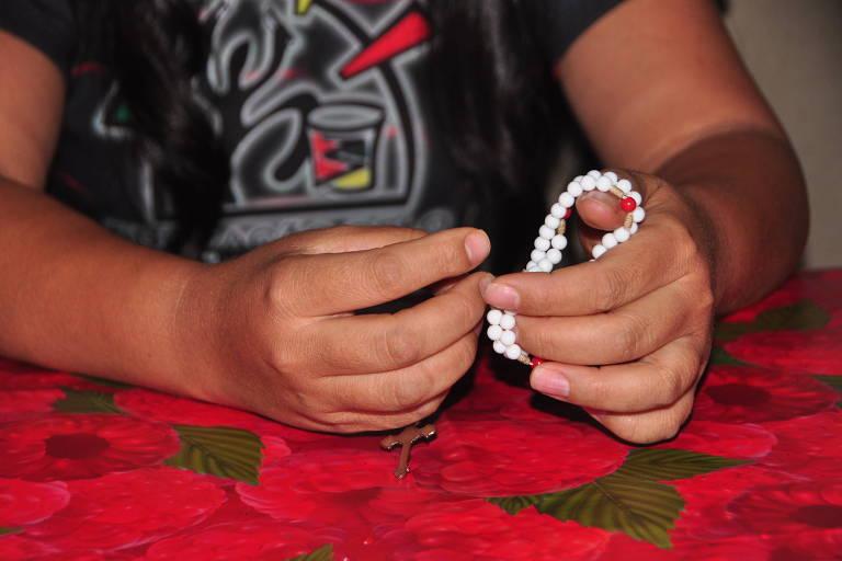 Mãos femininas pousadas sobre toalha de mesa vermelha seguram um terço branco