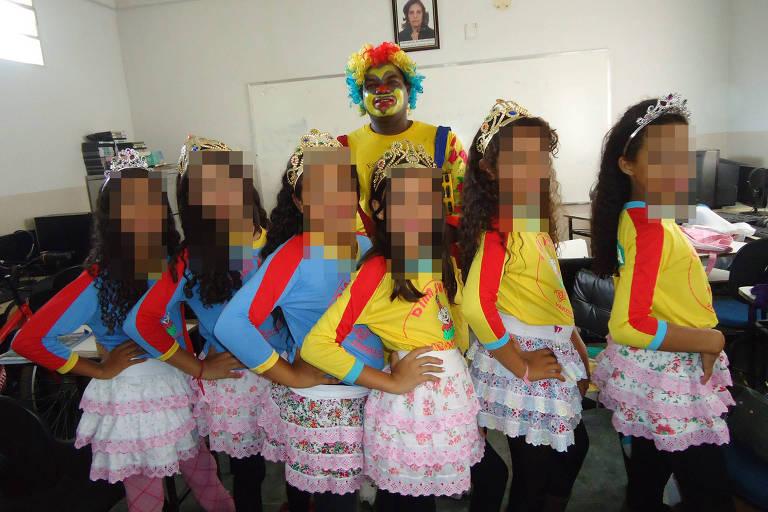 Homem vestido de palhaço posa em salão fechado com seis meninas de cerca de dez anos, usando tiara de princesa, camiseta amarela e saia curta de babados à frente, todas com a mão na cintura