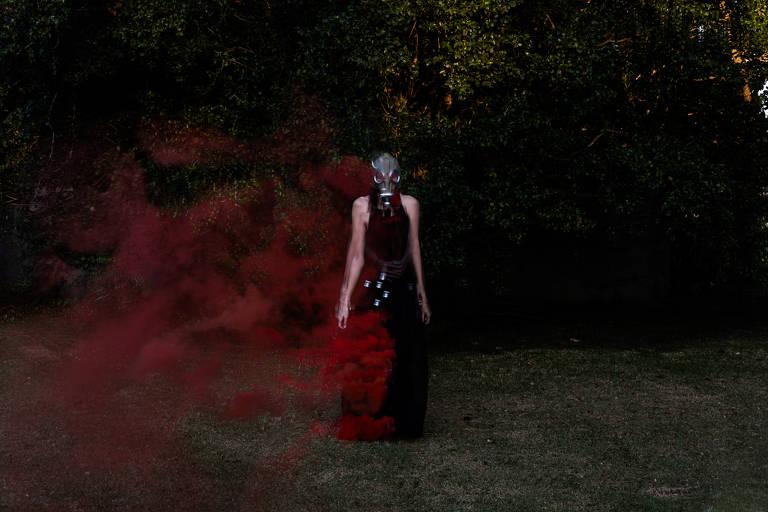 Mulher veste máscara que cobre totalmente seu rosto e fumaça vermelha circula sobre o ar