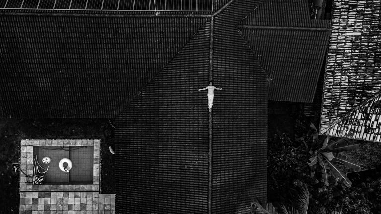 Pessoa aparece deitada com braços esticados sobre telhado de sua casa. Foto feita por drone