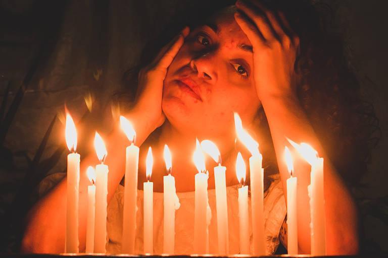 Rosto de mulher aparece sob luzes de velas