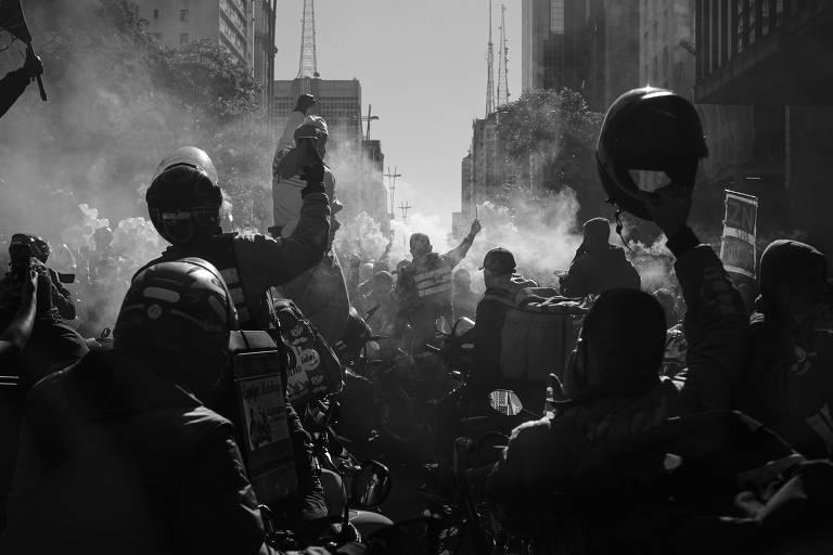 Foto em branco com motoristas erguendo capacete em protesto