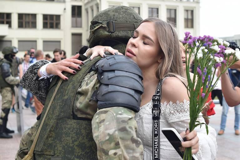 Manifestante abraça agente de segurança de Belarus durante protesto contra autocrata Alexandr Lukachenko, em Minsk