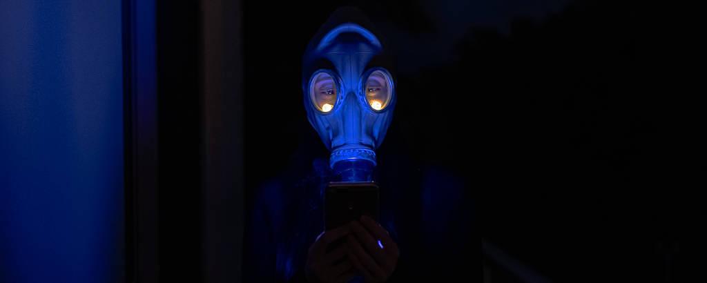Pessoa veste máscara química que cobre todo seu rosto, que está iluminado por uma luz azul em meio a uma escuridão