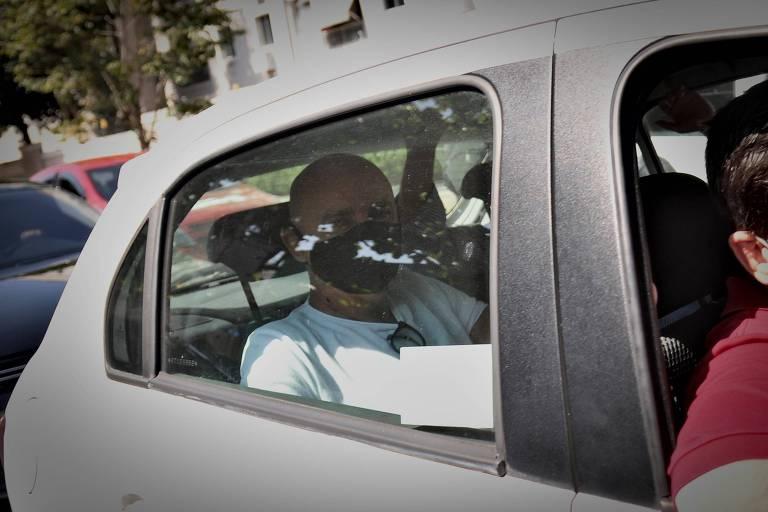 Dentro de um carro, Queiroz no banco de trás, usando máscara