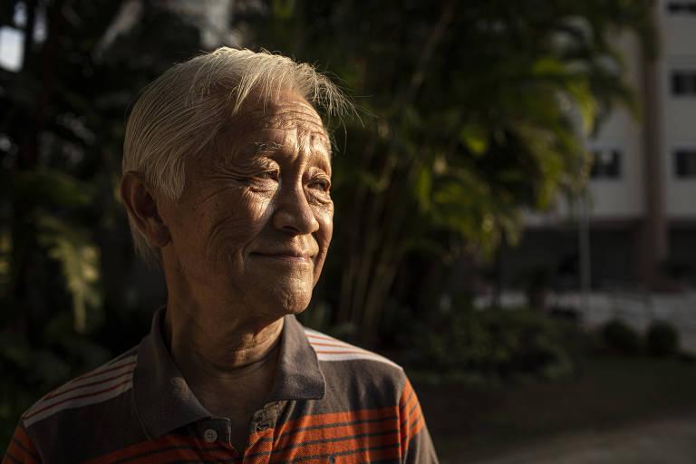 Rubens Chang Chung Lin, 78, chinês que imigrou para o Brasil aos 8 anos; é um homem magro, bronzeado, com cabelos totalmente brancos; a foto ele está no canto esquerdo, de camisa polo listada de cinza e laranja, olhando para a direita, e a o fundo há plantas e um prédio