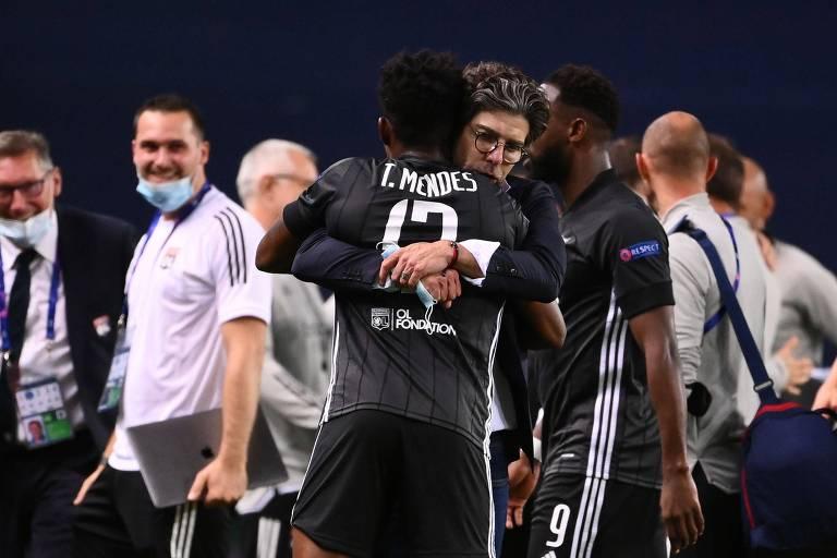 Juninho abraça o brasileiro Thiago Mendes após a vitória