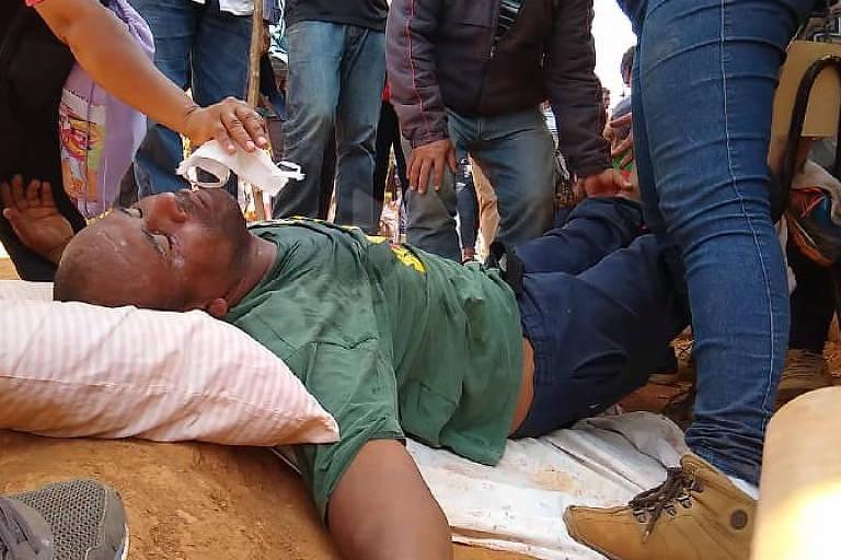 homem deitado no chão é socorrido por outras pessoas