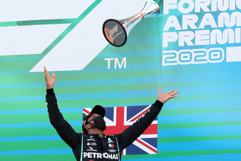 Hamilton joga seu troféu para o alto