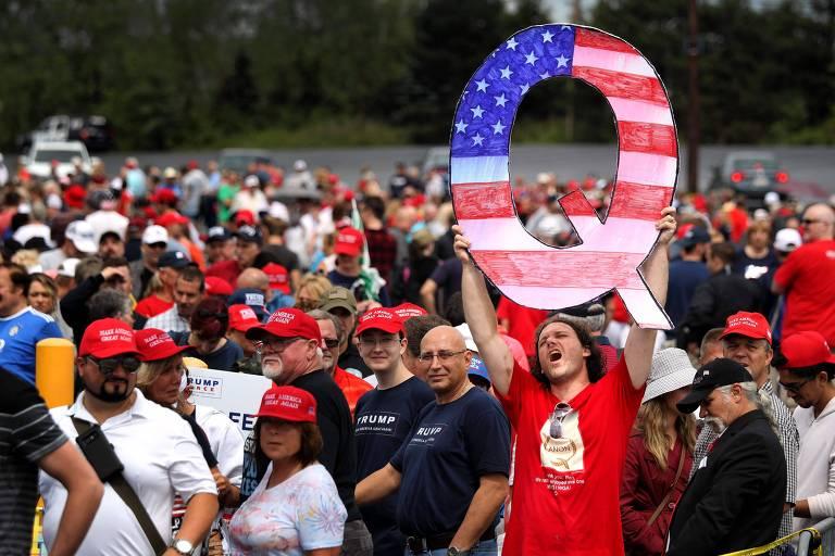 Apoiador de Donald Trump segura letra 'Q' com a bandeira americana enquanto aguarda o presidente em um comício na Pennsylvania