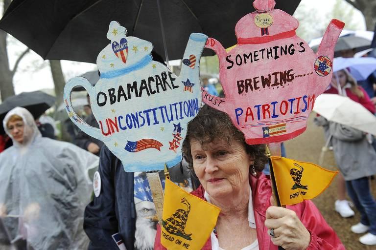Mulher segura cartazes contra o Obamacare em comício do movimento Tea Party