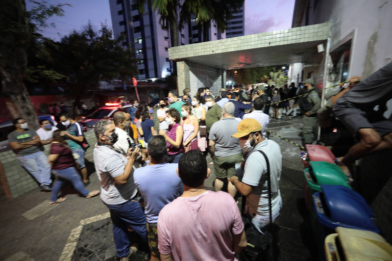 Pequena multidão se aglomera diante de marquise de hospital ao entardecer