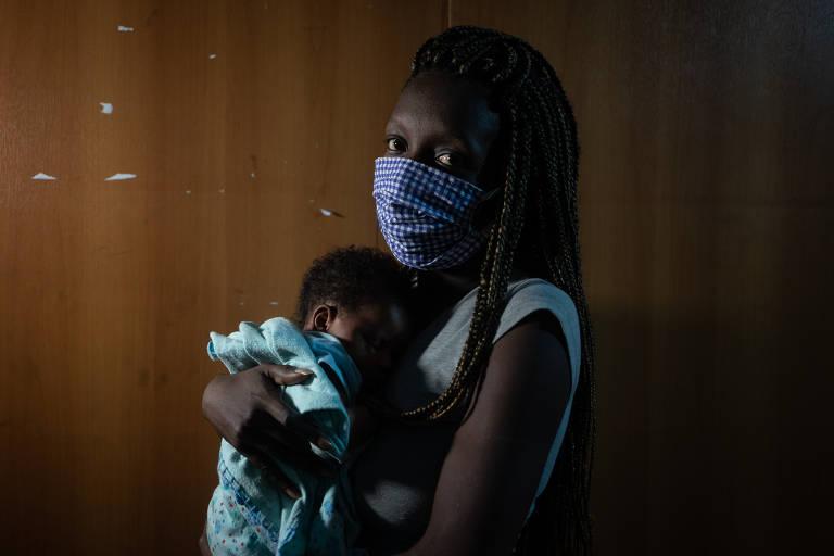 Uma mulher negra de tranças compridas e usando máscara segura um bebê no colo, que usa uma manta verde
