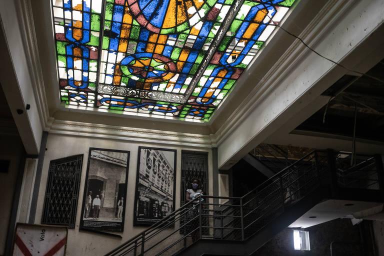 Hall de entrada de um prédio, com teto com vitrais coloridos e escada ao fundo, com quadros de cenas da cidade do Rio