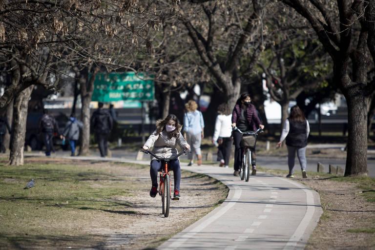 De máscara, menina anda de bicicleta vermelha em uma ciclovia em um parque.