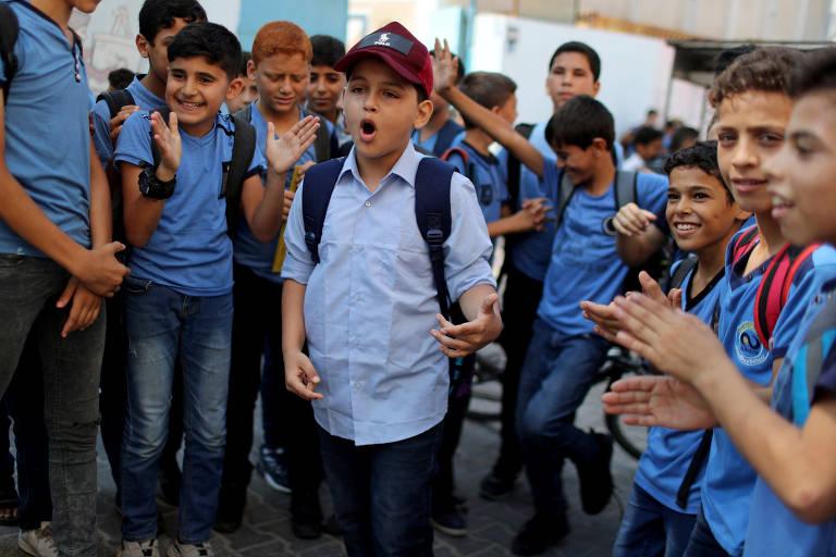 Abdel-Rahman Al-Shantti,( de boné vermelho)  um rapper de 11 anos de Gaza, está cercado por alunos enquanto se apresenta em sua escola na cidade de Gaza