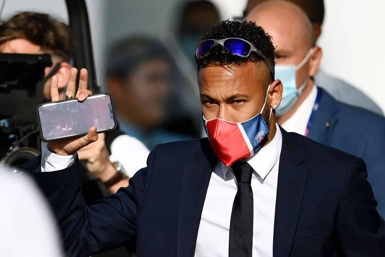 Neymar, de terno e óculos escuro espelhado na cabeça, com celular na mão, acena
