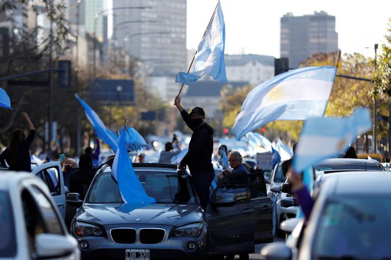 Homem de máscara e boné com o corpo pra fora de seu carro BMW balança bandeira da argentina.