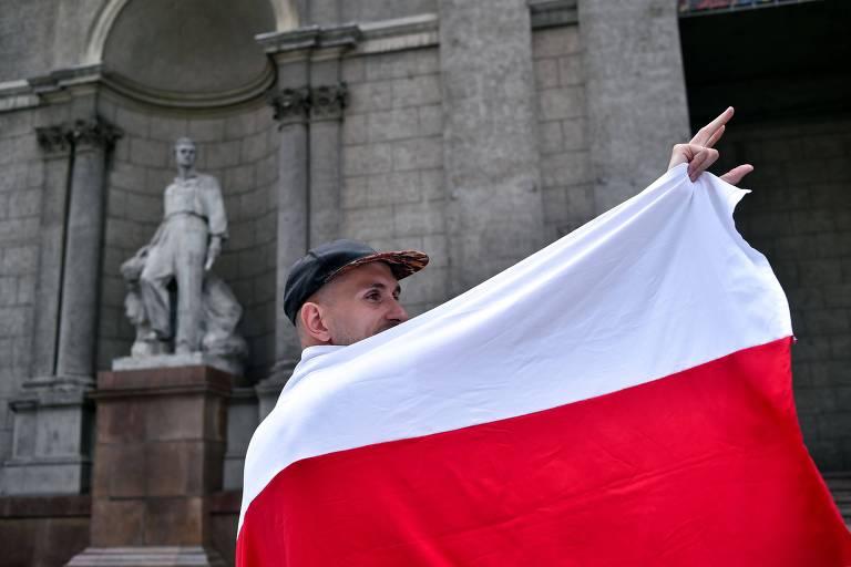 Homem enrolado na antiga bandeira da Belarus acena a funcionários do Museu Nacional de Arte, em Minsk