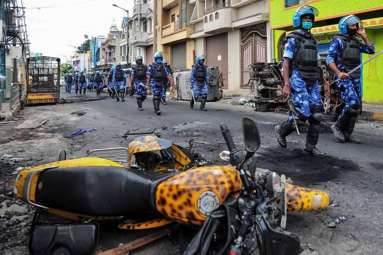 Policiais patrulham rua em Bangalore após tumulto ocorrido devido a post depreciativo contra Maomé no Facebook