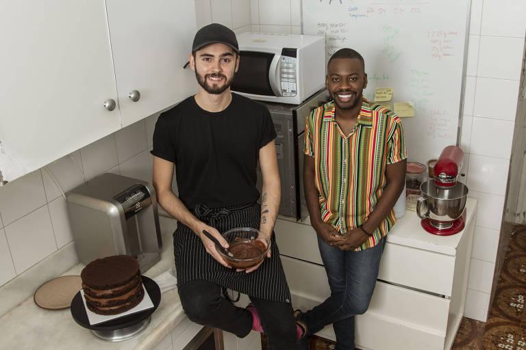 Confeiteiro Henrique Rossanelli está sentado em cima da bancada da cozinha segurando pote de mistura de doce. Ao lado, o sócio Igor Oliveira sorri.