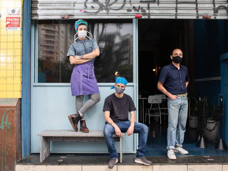 A chef Bel Crozera e seus dois sócios estão de máscara em frente à cozinha que alugaram.