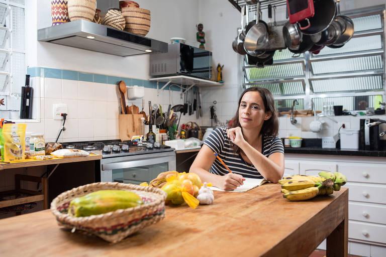 A chef Bel Coelho está sentada na mesa da cozinha de sua casa anotando em um caderno e olhando para a câmera