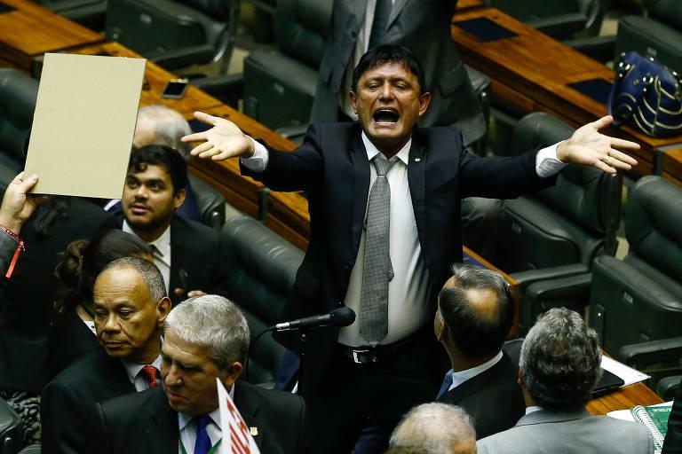 Eder com os braços abertos no meio das cadeiras do plenário, com vários parlamentares homens por perto