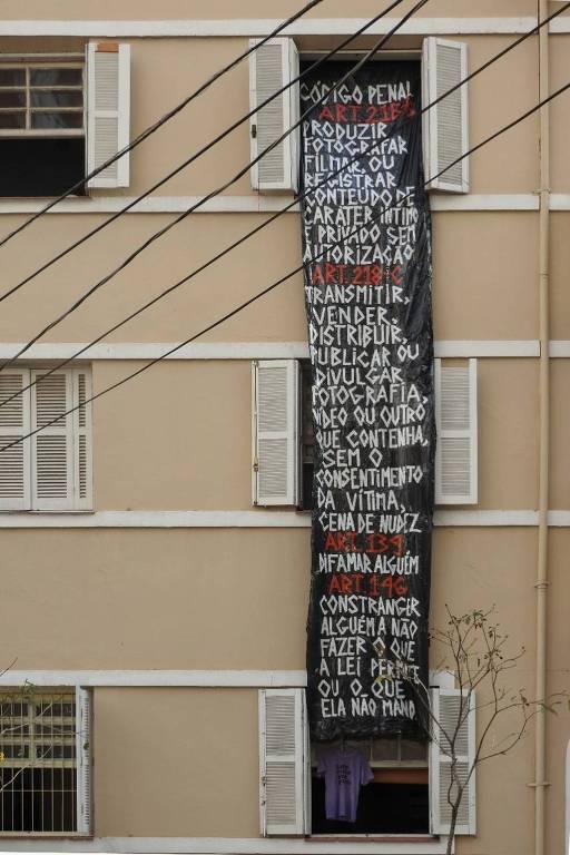 Mulher ergue cartaz com artigos do Código Legal em resposta a vizinhos que tirar fotos suas em casa