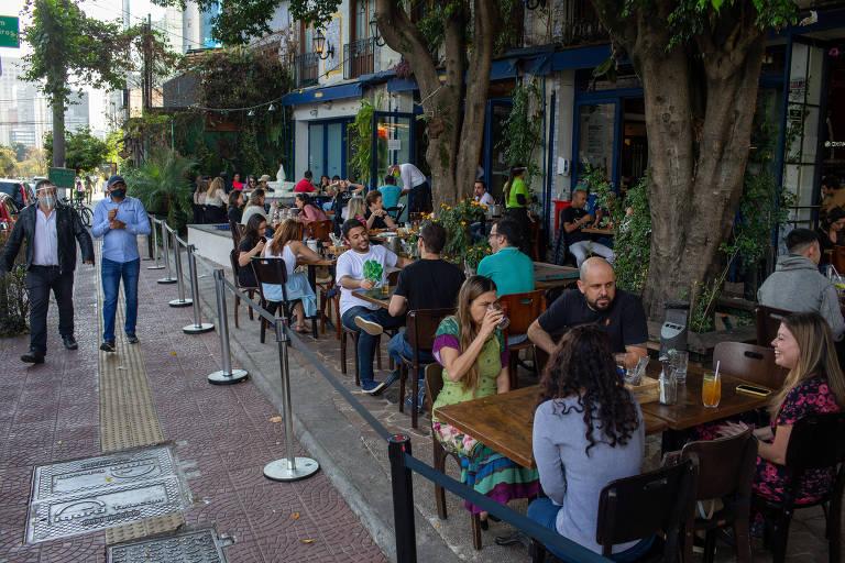 Mesas cheias de gente em calçada