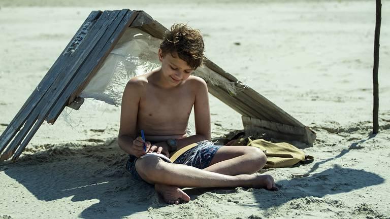 Um menino sentado na areia escrevendo em um caderno. Atrás dele, há uma estrutura de madeira no chão, formando uma espécie de cabana