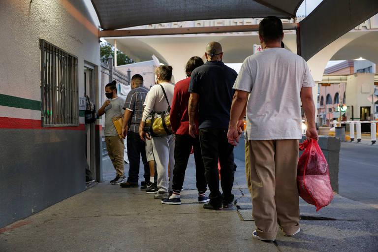 Trabalhadores deportados dos EUA passam por posto de controle em Ciudad Juarez, no México
