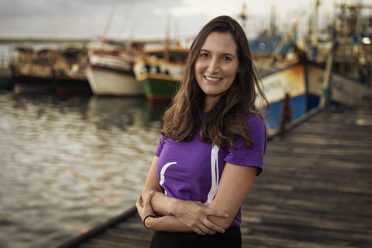 Bárbara posa para a foto sorrindo e de braços cruzados. Está em um píer com barcos de pescadores ao fundo