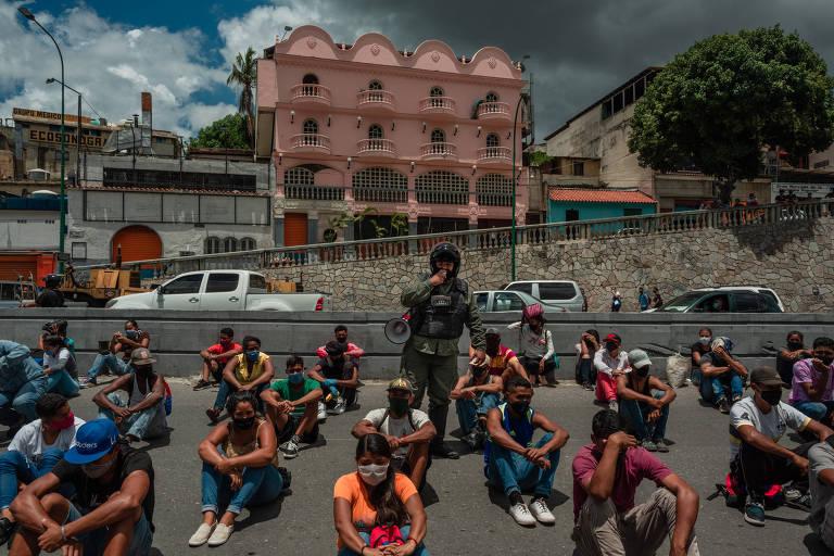Policial retém cidadãos por horas para explicar a importância da quarentena, em Caracas