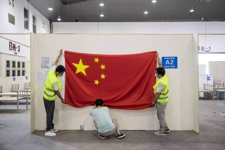 Três trabalhadores chineses removem bandeira do país da parede.