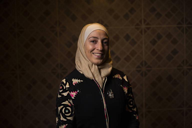Ghazal Baranbo, imigrante síria que vive em São Paulo com seus três filhos e marido; é uma mulher de olhos escuros, tez morena, usa a cabeça coberta por um xale bege e veste uma blusa de lã preta, com as mangas estampadas em bege e vermelho; ela posa na frente de uma parede de ladrilhos em tom de bege e marrom