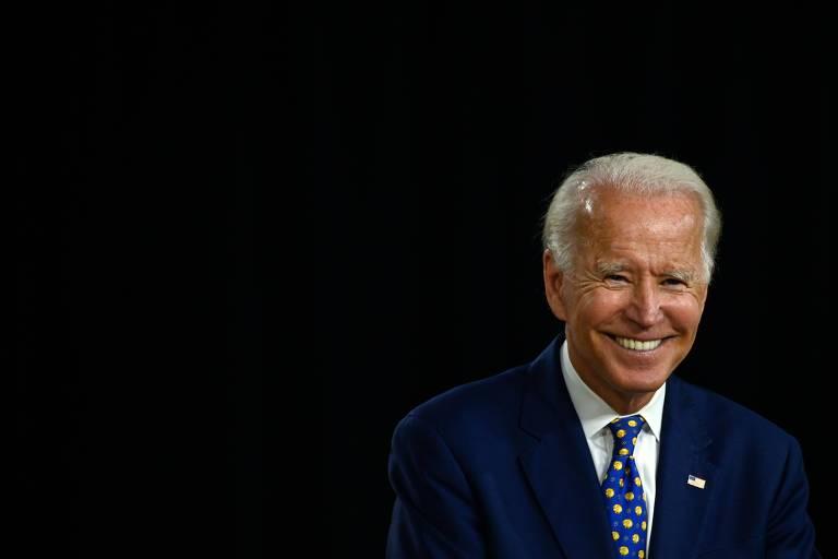 Joe Biden sorri sobre fundo preto.