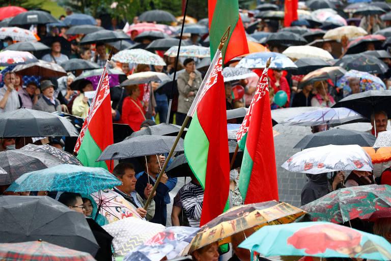 Manifestantes pró-Lukachenko com bandeiras da Belarus, em Minsk