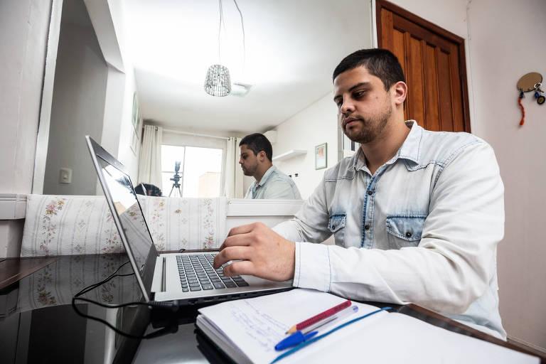 Lucas utiliza o computador na sala de sua casa, com um caderno aberto sobre a mesa.