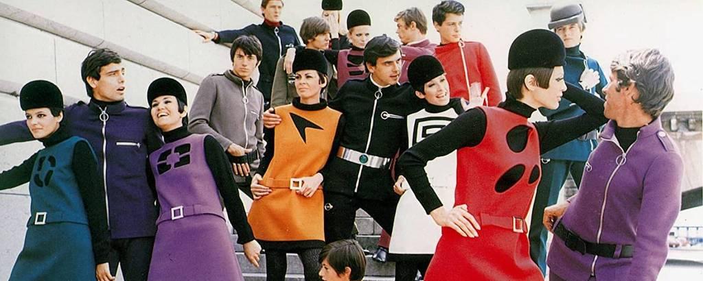 Várias pessoas usam roupas coloridas, chapéus pretos e trajes autênticos